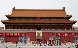 Athletes run past a portrait of late Chinese Chairman Mao Zedong at the entrance to the Forbidden City during the women's marathon at the 15th IAAF Championships in Beijing, China August 30, 2015.  REUTERS/Kim Kyung-Hoon