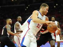 April 20, 2016; Los Angeles, CA, USA; Los Angeles Clippers forward Blake Griffin (32) moves the ball as  Portland Trail Blazers forward Al-Farouq Aminu (8) pulls his jersey during the second half at Staples Center. Mandatory Credit: Gary A. Vasquez-USA TODAY Sports