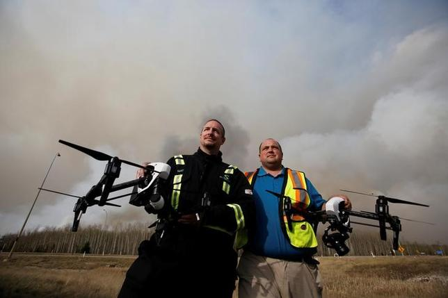 Mat Matthews, operations and safety manager with Elevated Robotic Services, and Ron Windmueller, owner of Droneology, pose with drones as smoke rises from wildfires near Fort McMurray, Alberta, Canada, May 6, 2016. REUTERS/Chris Wattie