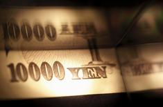 Light is cast on a Japanese 10,000 yen note as it's reflected in a plastic board in Tokyo, in this February 28, 2013 picture illustration.   REUTERS/Shohei Miyano/File Photo