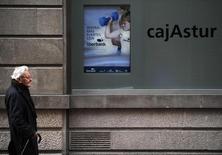 Liberbank anunció el miércoles una caída del 33,1 por ciento de su beneficio atribuido en los tres primeros meses del año a 38 millones de euros, afectado por los menores tipos de interés. En la imagen, un hombre camina delante de la sede de Cajastur, parte de Liberbank, en Oviedo, España, el 20 de diciembre de 2012. REUTERS/Eloy Alonso