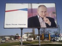 Рекламный щит с портретом президента России Владимира Путина в Крыму. Россия достроила энергомост в аннексированный Крым, подключив последнюю его линию в среду и увеличив мощность перетока из энергосистемы юга до 800 мегаватт, что должно полностью обеспечить спрос на полуострове.  REUTERS/Andrew Osborn