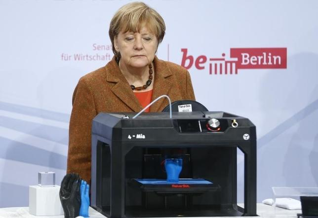 German Chancellor Angela Merkel looks at a 3D printer during a visit to the 9th national IT summit in Berlin, Germany, November 19, 2015. REUTERS/Hannibal Hanschke