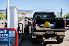 Eddie MacDonald fills his truck with gas in Wandering River, Alberta, after evacuating Fort McMurray due to raging wildfires on May 6, 2016. REUTERS/Topher Seguin