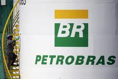 Un trabajador pintando un estanque de Petrobras en Brasilia, sep 30, 2015. La petrolera brasileña Petrobras prevé terminar el año con un saldo final de caja de 21.000 millones de dólares, que se compara con los 26.000 millones de principios de año, según el flujo de caja presentado el viernes por la empresa a analistas e inversores.  REUTERS/Ueslei Marcelino