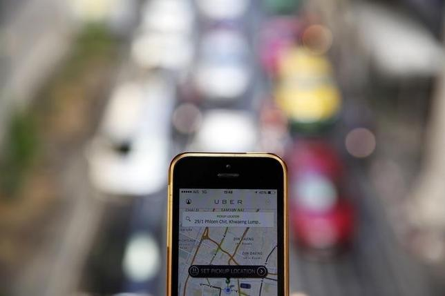 A phone running the Uber application is held above the traffic in central Bangkok December 10, 2014. REUTERS/Damir Sagolj/Files