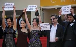 """Director Kleber Mendonca Filho (2ndR) and cast members Maeve Jinkings (L), Sonia Braga (2ndL), Carla Ribas (C) and Irandhir Santos hold placards to protest against the impeachment of suspended Brazilian President Dilma Rousseff on the red carpet as they arrive for the screening of  the film """"Aquarius"""" in competition at the 69th Cannes Film Festival in Cannes, France, May 17, 2016.  REUTERS/Jean-Paul Pelissier"""