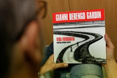 """A man holds the catalogue of the exhibition titled """"True photography"""" by Italian photographer Gianni Berengo Gardin in Rome May 23, 2016. REUTERS/Stringer"""