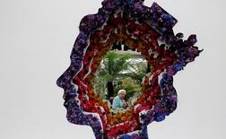 Britain's Queen Elizabeth II is pictured through a gap in a floral exhibit by the New Covent Garden Flower Market, which features an image of the Queen, during a visit to the 2016 Chelsea Flower Show in central London May 23, 2016. REUTERS/Adrian Dennis/Pool.