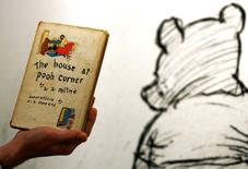 An employee poses with the first American edition of A.A. Milne's Winnie-the-Pooh book 'The House at Pooh Corner' dated 1928 at Sotheby's in London December 15, 2008.  REUTERS/Luke MacGregor