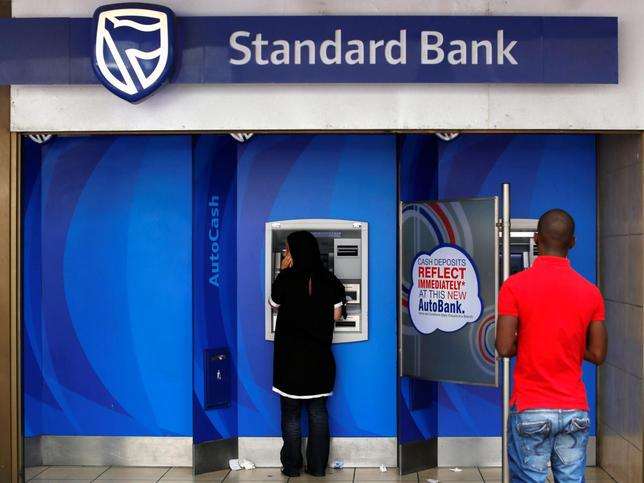 Customers queue to draw money from an ATM outside a branch of South Africa's Standard Bank in Cape Town, March 15, 2016. REUTERS/Mike Hutchings