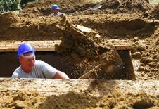 A gravedigger takes part in the first Hungarian grave digging championship in Debrecen, Hungary, June 3, 2016, competing for the national crown, which is awarded based on accuracy, speed, and aesthetic quality.   REUTERS/Laszlo Balogh