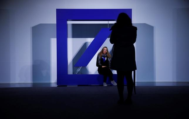 People pose for pictures with the emblem of Deutsche Bank during the bank's annual general meeting in Frankfurt, Germany, May 19, 2016.    REUTERS/Kai Pfaffenbach