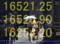 Una mujer en kimono se refleja en un tablero que muestra el índice Nikkei, afuera de una correduría en Tokio, Japón. 18 de abril de 2016. El índice Nikkei de la bolsa de Tokio cayó el viernes después de que el rendimiento de los bonos soberanos a 10 años tocó un mínimo histórico, lo que agitó a los inversores ya cautelosos antes de las decisiones de política monetaria de la Reserva Federal de Estados Unidos y el Banco de Japón la próxima semana. REUTERS/Toru Hanai