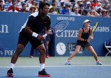 Leander Paes of India plays with mixed doubles partner Martina Hingis of Switzerland during their finals match against Bethanie Mattek-Sands and Sam Querrey of the U.S. at the U.S. Open Championships tennis tournament in New York, September 11, 2015.  REUTERS/Shannon Stapleton