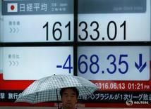 Пешеход проходит мимо экрана с коитровкой индекса Nikkei в Токио 13 июня 2016 года. Японский фондовый рынок завершил торги четверга на четырехмесячном минимуме, поскольку бездействие Банка Японии, осторожность ФРС США, вызвавшая укрепление иены, и опасения по поводу возможного выхода Британии из Евросоюза создали предпосылки для распродажи на рынке акций. REUTERS/Issei Kato