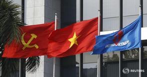 Флаг PetroVietnam (справа), флаг Вьетнама (в центре) и флаг Коммунистической партии Вьетнама в Ханое 11 января 2016 года. Роснефть и вьетнамская Petrovietnam подписали контракт на поставку до 96 миллионов тонн нефти в период до 2040 года, сообщила российская компания в своем пресс-релизе. REUTERS/Nguyen Huy Kham