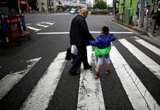 A man and his grandchild walk on the street at Tokyo's Sugamo district, an area popular among the Japanese elderly, in Japan June 15, 2016. REUTERS/Issei Kato