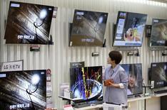 Женщина смотрит на телевизоры LG Electronics в магазине Сеула. Индийское подразделение южнокорейской LG Electronics Inc начало продажу телевизоров, имеющих функцию отпугивания москитов, которые являются переносчиками таких заболеваний, как малярия, вирус Зика и лихорадка денге.REUTERS/Kim Hong-Ji