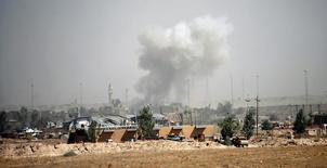 """Дым поднимается над столкновением иракских войск с боевиками ИГИЛ в Фаллудже. Иракская армия вернула контроль над местным административным зданием в городе Эль-Фаллуджа, которое было захвачено боевиками """"Исламского государства"""", сообщило государственное телевидение Ирака.  REUTERS/Thaier Al-Sudani"""