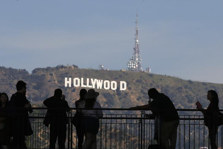 People look on and photograph the famed Hollywood sign as preparations continue for the 88th Academy Awards in Hollywood, Los Angeles, California February 26, 2016. REUTERS/Carlo Allegri