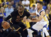 Jun 19, 2016; Oakland, CA, USA; Cleveland Cavaliers forward LeBron James (23) handles the ball against Golden State Warriors guard Stephen Curry (30) during the third quarter in game seven of the NBA Finals at Oracle Arena. Mandatory Credit: Bob Donnan-USA TODAY Sports
