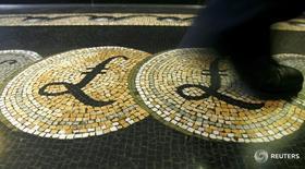 Мозаика с символом фунта стерлингов у здания Банка Англии в Лондоне 25 марта 2008 года. Фунт стерлингов растет в ходе торгов понедельника на фоне сдвига общественного мнения в Великобритании в пользу невыхода из Евросоюза, поддержавшего склонность к риску и отправившего безопасную иену вниз. REUTERS/Luke Macgregor/files