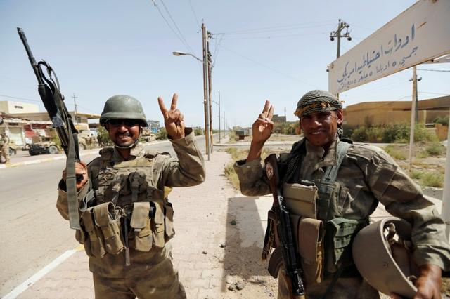 Iraqi soldiers gesture in center of Falluja. REUTERS/Thaier Al-Sudani
