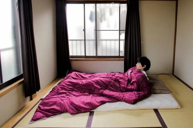 6月19日、オンライン出版の編集者である豊田克也さん(写真)の持ち物は、22平方メートルのアパートにテーブル1つと布団1組だけだ。都内で3月撮影(2016年 ロイター/Thomas Peter)