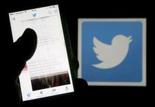 Un hombre lee tuits en su celular, frente a un logo de Twitter, en Bourdeaux, Francia. 10 de marzo de 2016. La red social Twitter, que limita sus mensajes a 140 caracteres, permitirá a sus usuarios publicar videos de hasta 140 segundos. REUTERS/Regis Duvignau/Illustration/File Photo
