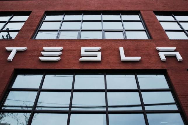 A Tesla logo hang on a building outside of a Tesla dealership in New York, U.S., April 29, 2016. REUTERS/Lucas Jackson