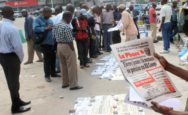 Residents read newspapers with reports of Yellow Fever, along the streets in Kinshasa, capital of the Democratic Republic of the Congo, June 21, 2016. REUTERS/Jean Robert N'kengo