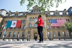 The Mexican and U.S. flags hang from the Langevin Block in advance of Wednesday's North American Leaders' Summit as a man waits for a bus by in Ottawa, Ontario, Canada, June 27, 2016. REUTERS/Chris Wattie