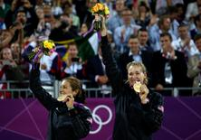 Gold medallists Misty May-Treanor of the U.S. and team mate Kerri Walsh Jennings (R) celebrate with their medals at the women's beach volleyball victory ceremony at the Horse Guards Parade during the London 2012 Olympic Games August 8, 2012.       REUTERS/Marcelo Del Pozo