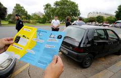 A man holds a leaflets as French police speaks to a driver with a car older than 20 years to explain a new law to fight air pollution at the Place de la Nation square in Paris, France, July 1, 2016.  REUTERS/Jacky Naegelen