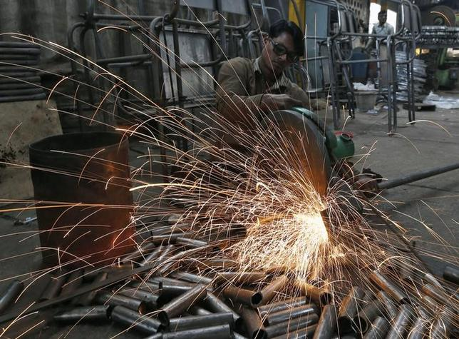 A worker cuts a metal pipe inside a steel furniture production factory in Ahmedabad February 2, 2015. REUTERS/Amit Dave/Files