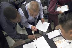 Personas buscando empleo rellenan formularios en una feria de trabajos en Los Ángeles, California. 4 de junio de 2015. Los empleadores privados de Estados Unidos abrieron en junio más puestos de trabajo de lo que esperaban los economistas, mientras que menos estadounidenses pidieron en la última semana el subsidio de desempleo, lo que sugiere un repunte en el crecimiento del empleo tras la débil cifra de mayo. REUTERS/David McNew