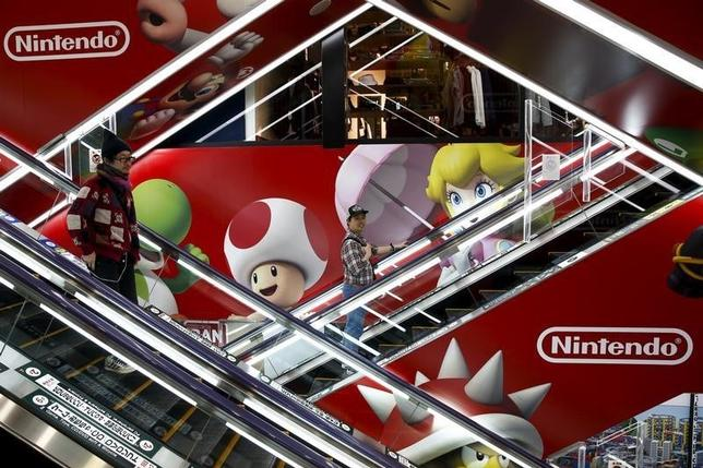 People ride escalators past an advertisement of the Nintendo Co videogame maker at an electronic retailer in Tokyo, Japan, April 25, 2016. REUTERS/Thomas Peter