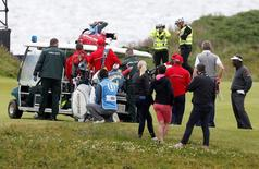 Golf - British Open - practice round - Royal Troon, Scotland, Britain - 12/07/2016.  Vijay Singh of Fiji (R) looks on as the caddie of U.S. golfer Marco Dawson is loaded onto an ambulance after he was struck by a golf ball.  REUTERS/Craig Brough