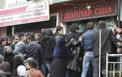 People gather near a currency exchange office in Dushanbe March 9, 2015. During the last week the average exchange rate of the U.S. dollar in the republic's exchange offices, rose and averaged 5.9930 - 6.0110 Tajikistan somoni, the National Bank of Tajikistan reported. In previous days, the average rates of exchange with the Russian rouble and the Euro also rose slightly and made 0,0960-0,0970 Somoni for one Russian rouble and 6.5990 - 6.6210 Somoni for one euro. REUTERS/Nozim Kalandarov (TAJIKISTAN  - Tags: BUSINESS) - RTR4SL0H