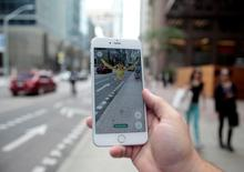 """A """"Pidgey"""" Pokemon is seen on the screen of the Pokemon Go mobile app, Nintendo's new scavenger hunt game which utilizes geo-positioning, in a photo illustration taken in downtown Toronto, Ontario, Canada July 11, 2016. REUTERS/Chris Helgren/File Photo"""
