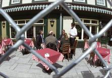 A waiter takes an order from a group of patrons lunching in an outside cafe near the summit security fence in Quebec City, April 18, 2001 in this file photo.