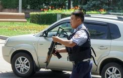 Полицейский бежит по улице в Алма-Ате 18 июля 2016 года. Власти Казахстана подозревают, что боевики, расстрелявшие в понедельник полицейских в крупнейшем городе страны - исламисты, сказал Рейтер источник в правоохранительных органах. REUTERS/Shamil Zhumatov