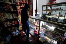 Un mujer atiende una tienda en el centro de Bogotá, Colombia.  3 de febrero de 2015. La confianza del consumidor en Colombia mejoró moderadamente en junio frente al nivel de mayo, aunque se mantuvo en terreno negativo, reveló el lunes una encuesta del centro de estudios económicos Fedesarrollo. REUTERS/Jose Miguel Gomez
