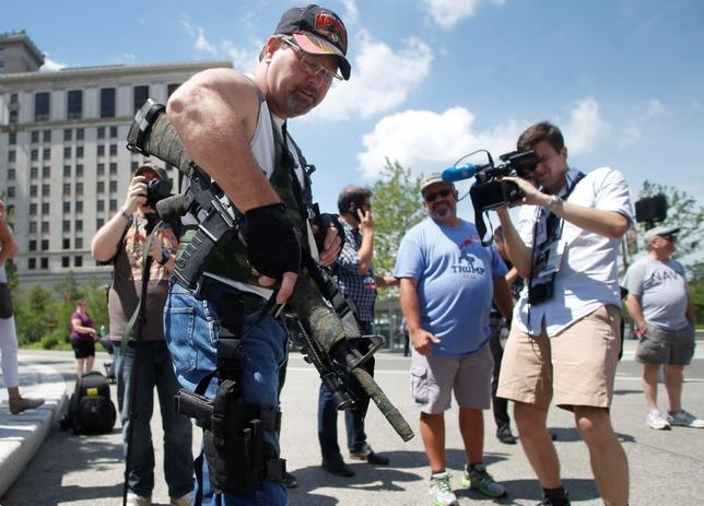 Steve Thacker carrying a rifle and a handgun is surrounded by members of the news media in Cleveland's public square in Cleveland, Ohio, U.S., July 17, 2016. REUTERS/Jim Urquhart/File Photo