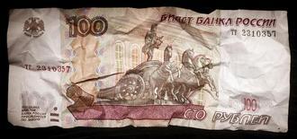 Мятая сторублевая купюра. Москва, 11 января 2016 года. Рубль может подешеветь в августе благодаря традиционному сезонному набору негативных для него факторов, таких как ухудшение текущего счета РФ, обратная конверсия полученных дивидендных выплат и низкий объем налоговых выплат, однако участники рынка не ждут его обвального падения вопреки опасениям, связанным с исторической памятью в отношении поведения российской валюты в последний летний месяц. REUTERS/Maxim Zmeyev