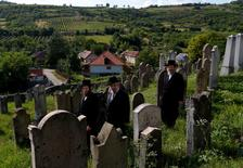 Three rabbis, the sons and grandson of a leading Hasidic rabbi Eliezer Ehrenreich walk in the cemetery in the village of Mad, Hungary, July 21, 2016. Picture taken July 21, 2016. REUTERS/Laszlo Balogh