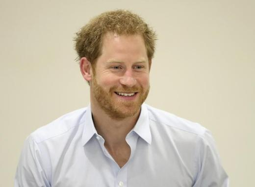 Prince Harry chats with staff during his visit to the Burrell Street Sexual Health Clinic in London, Britain on July 14, 2016. Photo: POOL New / Reuters