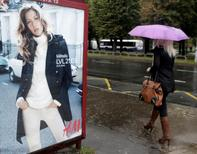 A woman walks past a H&M advertisement in Riga September 25, 2013.  REUTERS/Ints Kalnins