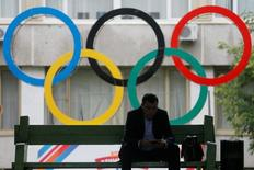 A man uses his tablet computer as he sits near Olympic rings placed in the courtyard of the Russian Olympic Committee headquarters in Moscow, Russia, July 22, 2016.  REUTERS/Maxim Shemetov